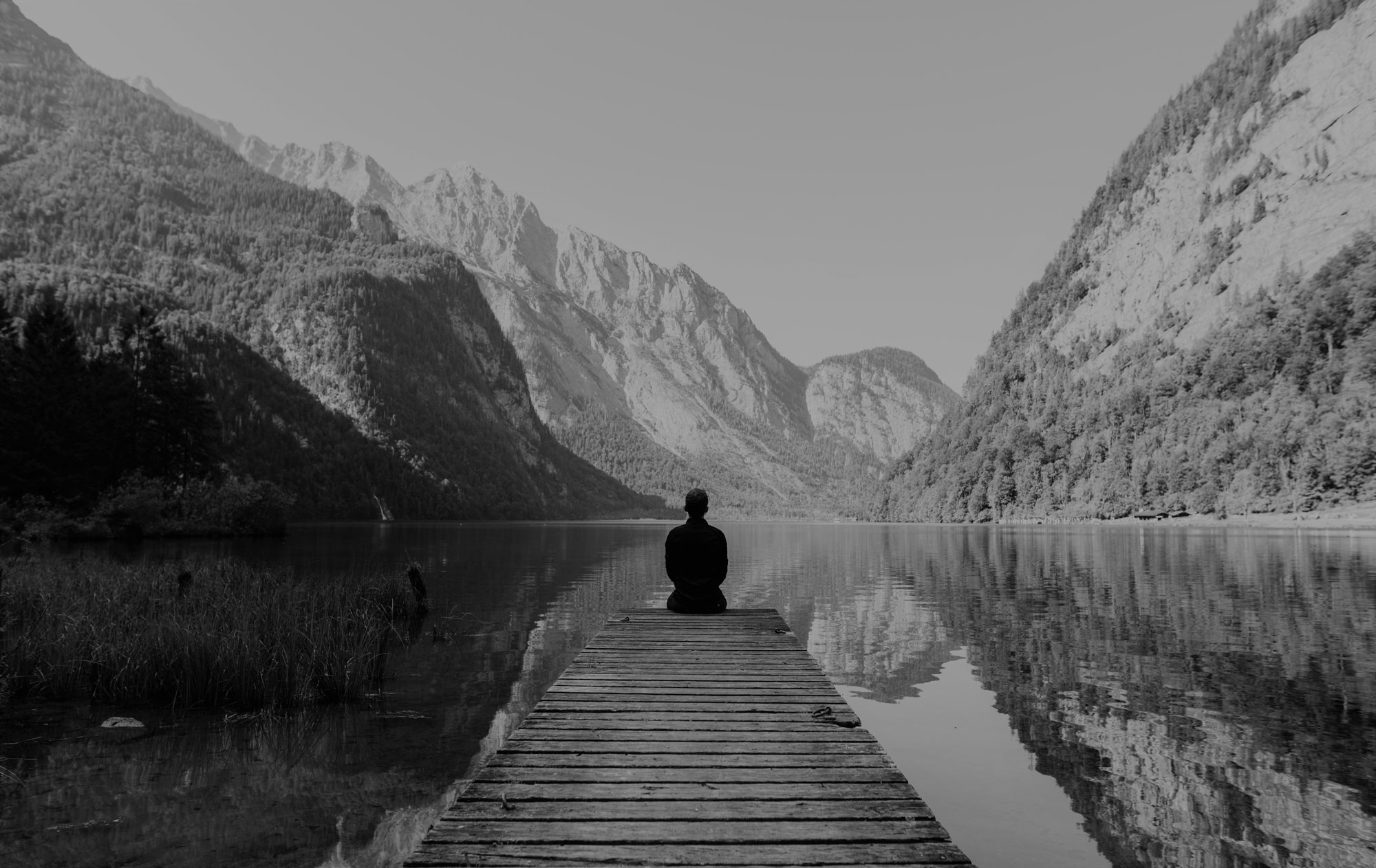 Man sitting on wood pier, in front of him a view of a lake and beautiful mountains