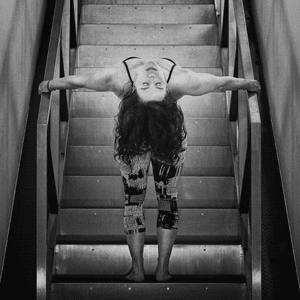 Doris Schernthaner steht mit Rücken auf den Treppen und lehnt sich zurück, sodass sich eine schöne Pose ergibt. Ihr Gesicht ist dadurch verkehrt sichtbar.