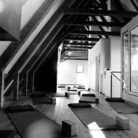 Leerer Raum mit 10 Yogamatten, jeweils mit Handtüchern. In schwarz-weiß