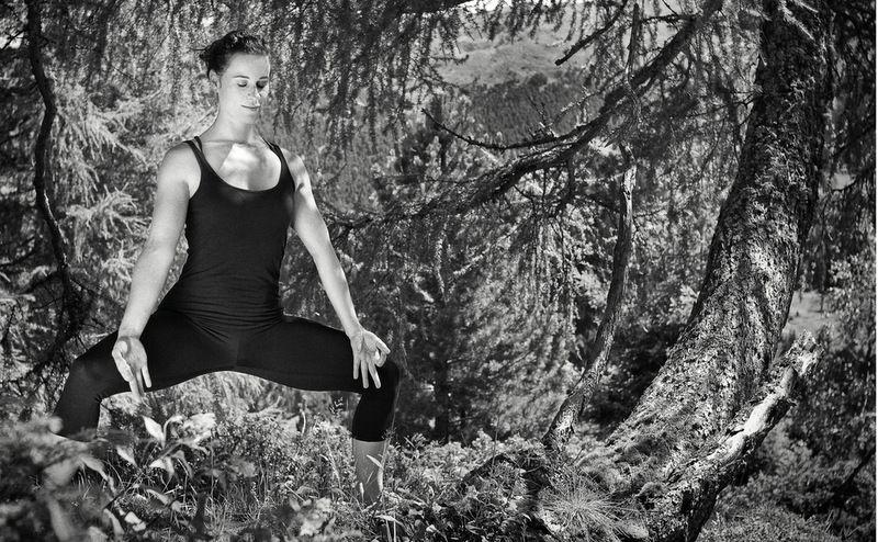 Doris Schernthaner in einer Yoga-Pose im Wald schwarz-weiß