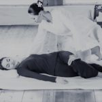 Young woman getting traditional thai stretching massage by therapist